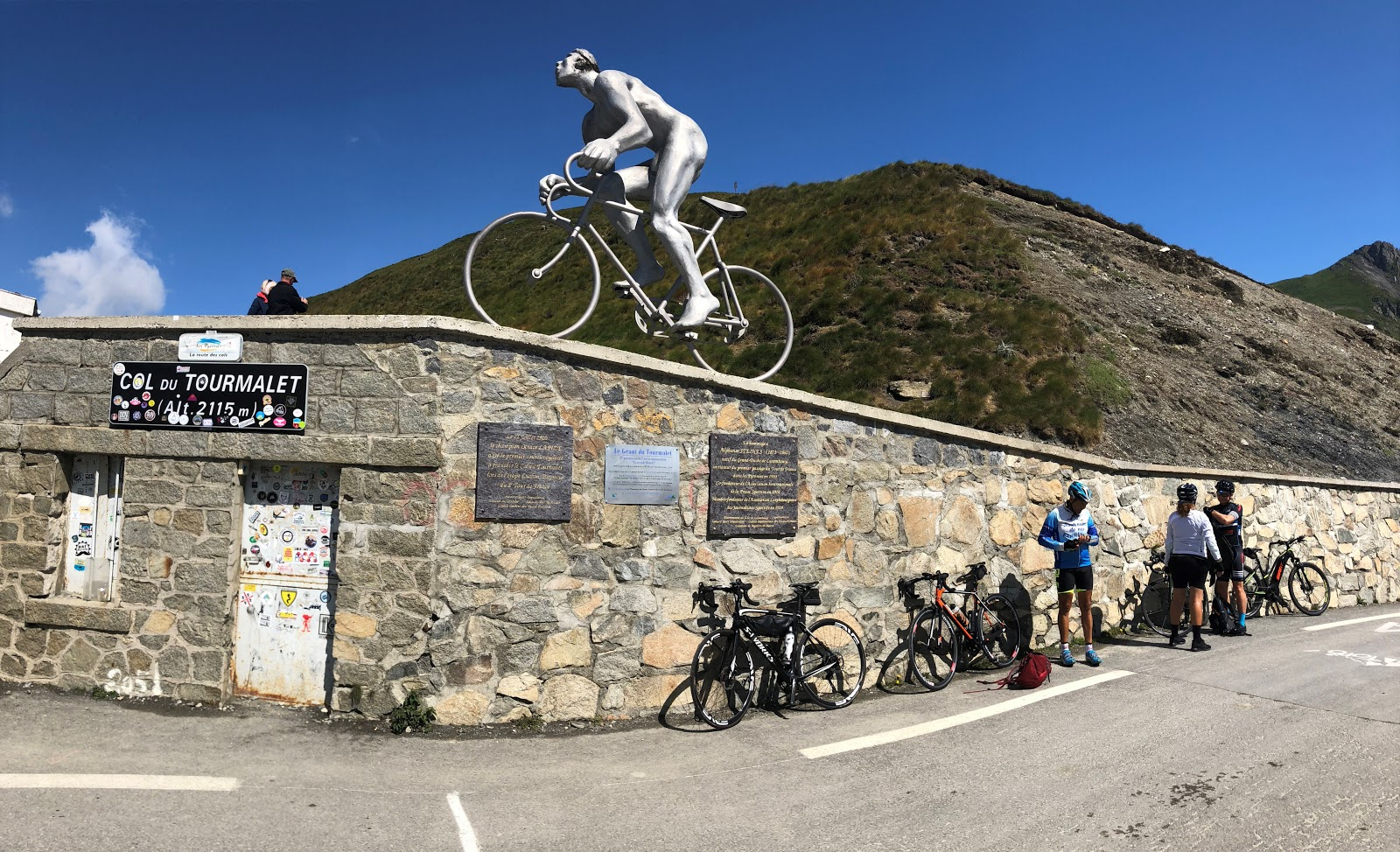 Bike climb up Col du Tourmalet - col - bicycles and cyclists; Le Geant statue, col sign