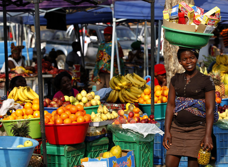 A woman walks through a market in Luanda, Angola. People who live in Africa's cities rely heavily on the informal sector.