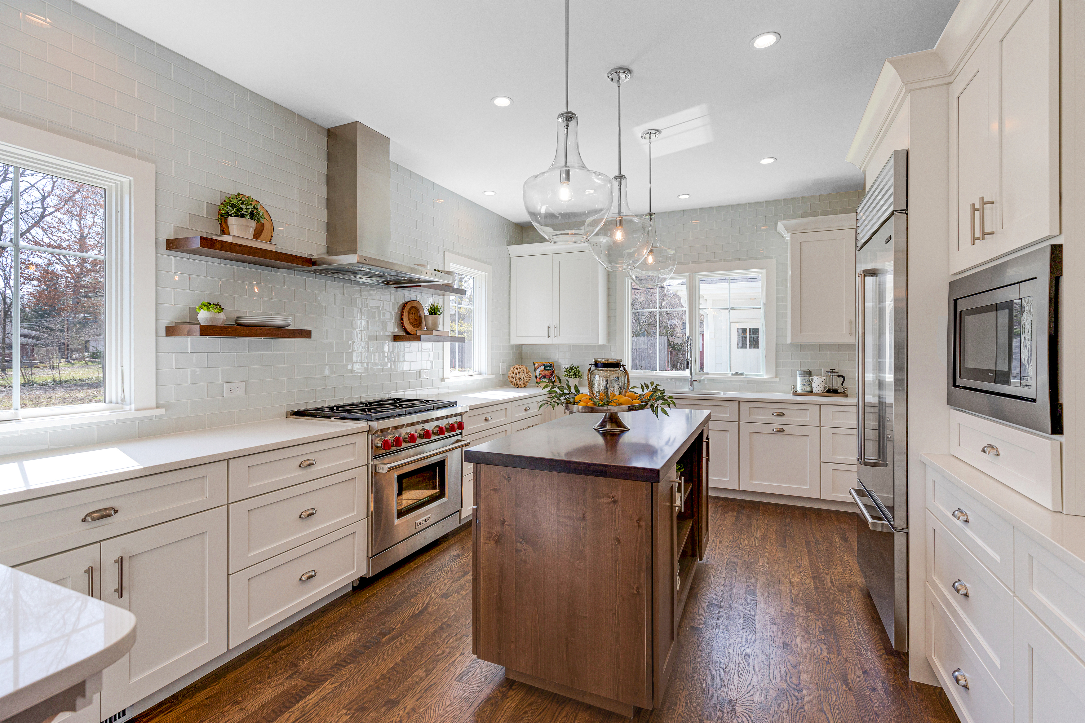 Kitchen with white cabinets, glass metro tiles, and featuring large glass pendant lights above a wood island