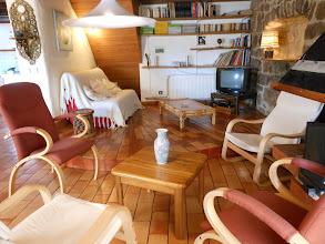 Photo: Au 1er plan : salon à côté de cheminée. Au 2ème plan : Bibliothèque avec TV, lecteur CD, DVD, radio, et canapé-lit 2 places. Espace très convivial !