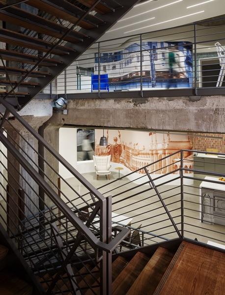 Blick von einer Holztreppe mit braunem Metallgeländer zwischen zwei Treppenläufen im Büro von Google in Chicago