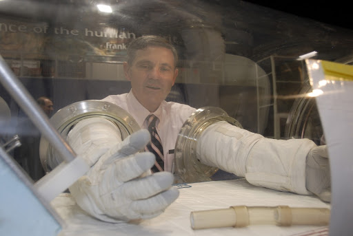 Kennedy Director Bob Cabana a former astronaut tries out a pair of space gloves part of NASA's Centennial Challenges Program.