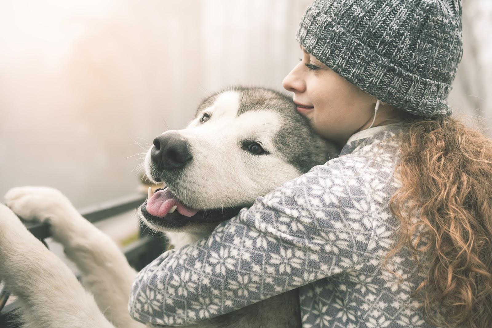 A woman hugging her husky outside