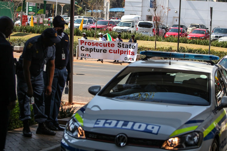 Members of the police enter the building as picketers from Organisation Undoing Tax Abuse (Outa) stage a protest outside the State Capture Inquiry in Parktown, Johannesburg.
