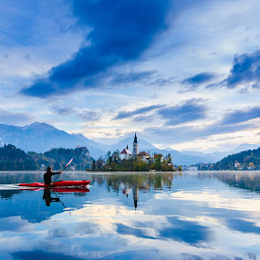Morning recreation by Andrej Folo - Landscapes Waterscapes ( clouds, mountain, church, moment, reflections, cloudscape, lake, recreation, morning, landscape, kayak, photography, landmark, blue sky, red, blue, slovenia, bled, cloudy, nikon )