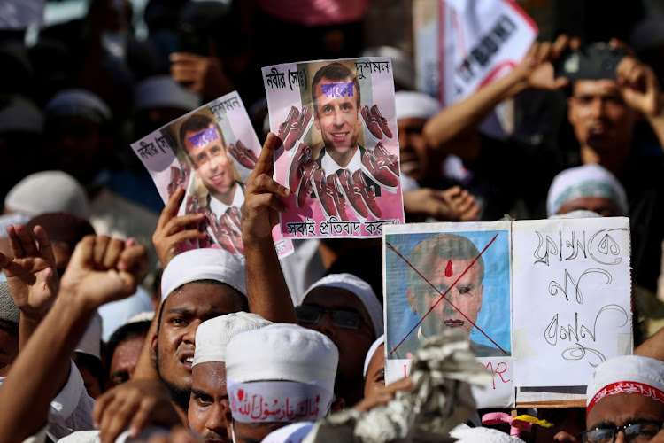 Muslims hold pictures of the French President Emmanuel Macron during a protest calling for the boycott of French products and denouncing Macron for his comments over Prophet Mohammed's caricatures, in Dhaka, Bangladesh, October 30 2020. Picture: REUTERS/MOHAMMAD PONIR HOSSAIN