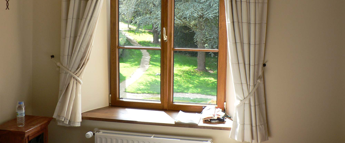 A view of a garden from a window with cleaned curtains