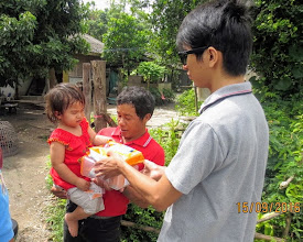 Photo: Sanpatong: one of the twins receives her formula milk.  With her father and Arm
