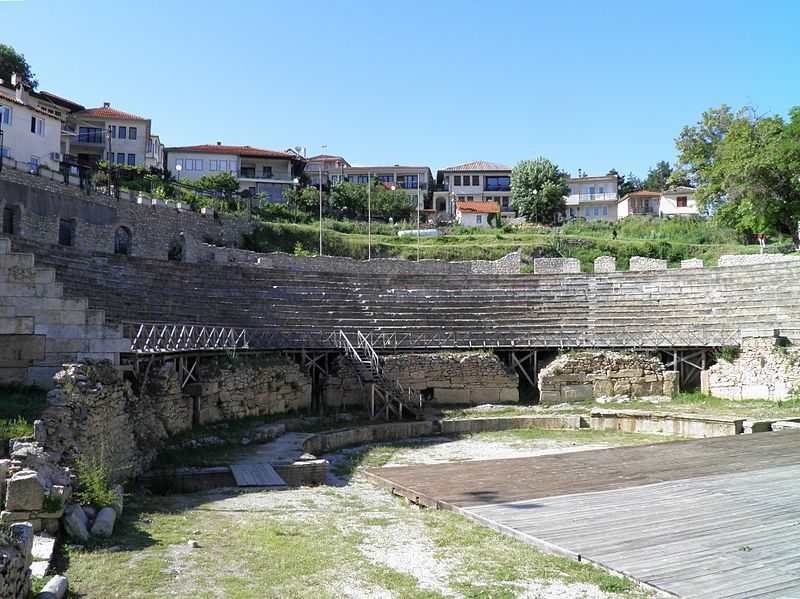 Present-day picture of an ancient Greek theater with houses in the background.