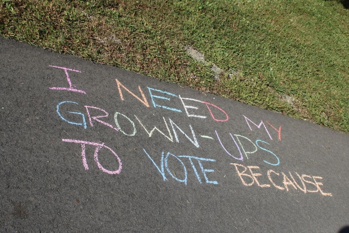 "Chalk drawing that reads: ""I need my grown-ups to vote because"""