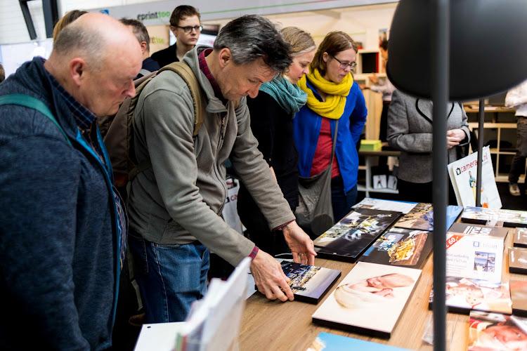 bezoekers bekijken en voelen aan foto's op het Bloxit systeem