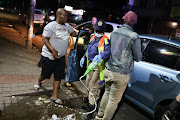 Law enforcement officials confiscate and pour alcohol onto a street in Johannesburg at the start of lockdown.