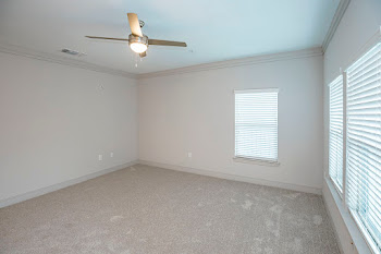 B2 living room with neutral carpet and ceiling fan
