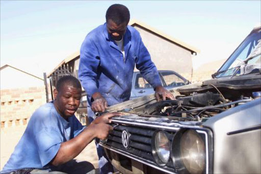 A group of people in Mamelodi, Tshwane, work for the Ntiro Project, the only programme in SA helping intellectually impaired people to find jobs or at least undergo on-the-job-training so they can become financially independent. Christopher Ramoshaba (left)  was trained by the Ntiro Project and now works for Boy Madzivane as a panel beater. 2/8/01. Pic: Simon Mathebula. © ST.