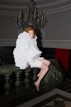 Photograph of a pale skinned, ginger haired model, wearing an ornate ruffled and ruched white dress, sitting on a marble balustrade
