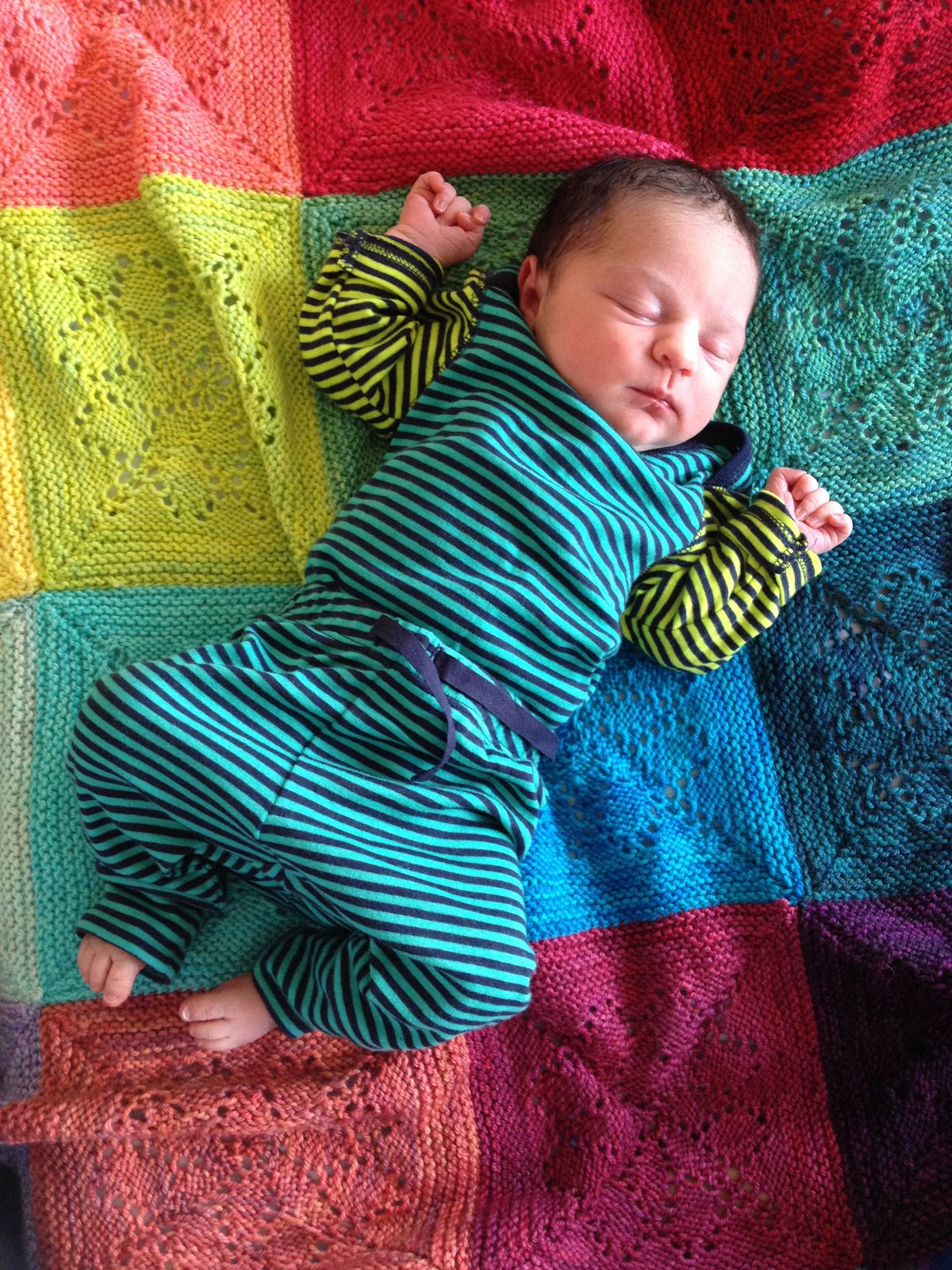A little baby bodhi in a dark blue and turquoise tracksuit that is a little too big.  She lay on her back on her hand-knitted blanket in a rainbow of squares.