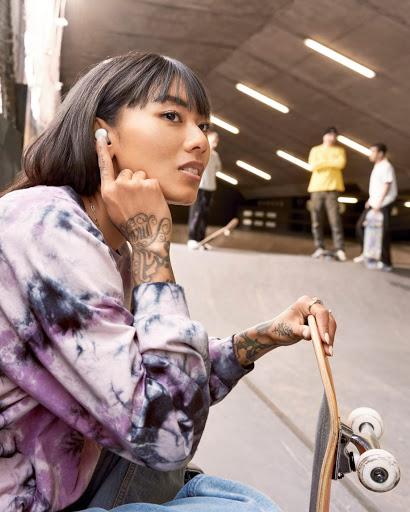 スケートボードを膝に立てかけてスケートパークで休憩するスタイリッシュな若い女性。この女性は曲をスキップしようと Google Pixel Buds A-Series に手を伸ばしている。