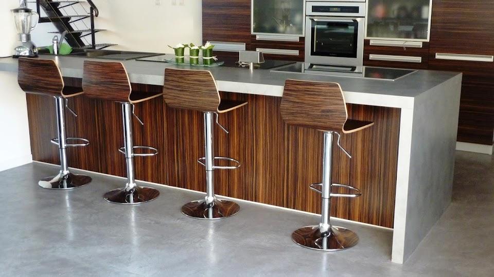Cuisine design et conviviale avec sol et plan de travail enduit en béton ciré