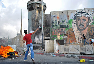 Photo: A Palestinian youth begins throwing rocks at a military watchtower stationed by Israeli soldiers at Qalandiya checkpoint. (SOLD)