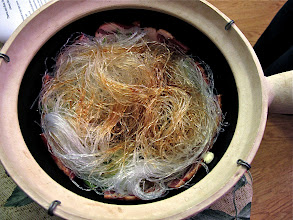 Photo: softened bean thread noodles added to claypot and sprinkled with fish sauce and black soy sauce