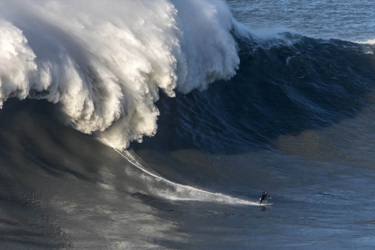 Andrew Cotton drops a wave during a surf session at Praia do Norte on November 8, 2017 in Nazare, Portugal. Cotton suffered a broken back after the wave knocked him off his board.