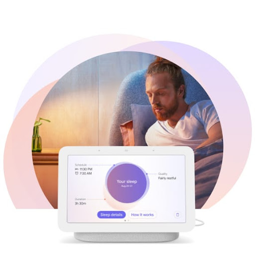 [Image] A man is sitting upright in bed turning toward his Nest Hub display at his bedside. It shows personalized insights about his sleep.