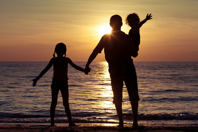 Father and children playing on the beach at sunset.