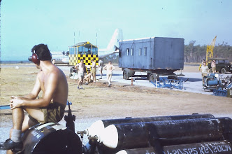 Photo: A 74 Sqn ground crew member sits on an oxyen trolley watching a Hercules taxi past.