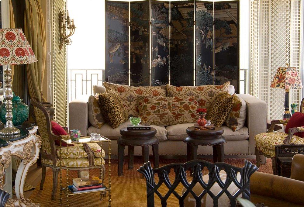 Sofá com almofadas coloridas, poltronas, e bancos de enfeite.