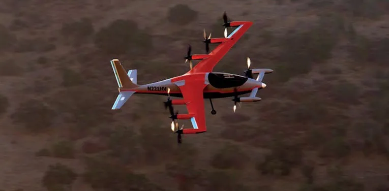 An orange colored electric aircraft with  6 propellers on its wings.