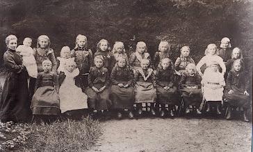 Photo: Handwerkclubje v.l.n.r. Zittende: Fennechien Oosting, Geessien Essing, Mattie Oosterhoff, Fennechien Jager, Jantje Koops, Jantje Lunshof, ??? Wever, Lammechien Braams en Marchien Homan. Staande: moeder met baby, Roelfien Hadderingh, Eppie de Jong, Jantje Sloots, Grietje Oosterhoff, ??? , Grietje Koops, Grietje Wilms, Annechien Jager, Giene Braams en Christiena Udding. Achteraan met oorijzer: Harmpje Vedder-Rutgers (Roef Vedders Harmie)