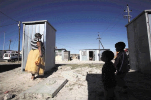 Nothemba Mpemyama and her children inspect newly enclosed toilets in Makhaza, Cape Town. The municipality has started enclosing all 1 316 units after residents approved a prototype Picture: SHELLEY CHRISTIANS