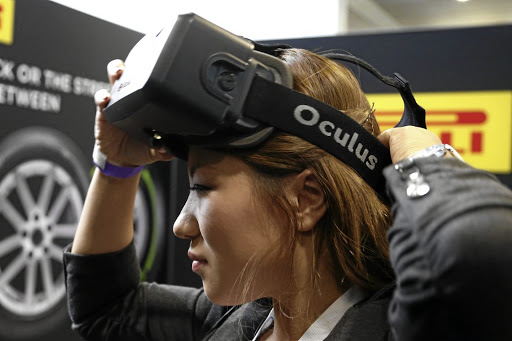 Reality check: A woman puts on an Oculus virtual reality headset during preparations for a trade show in Los Angeles in 2014. Picture: REUTERS