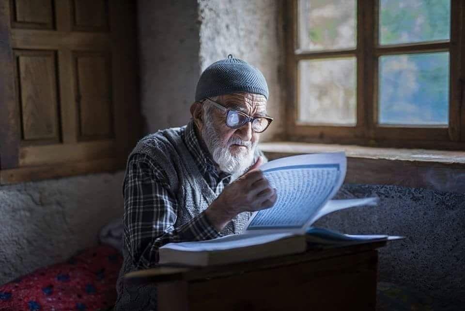 Homem idoso lendo Alcorão