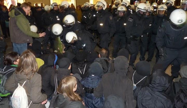 Polizisten und sitzende Demonstranten.