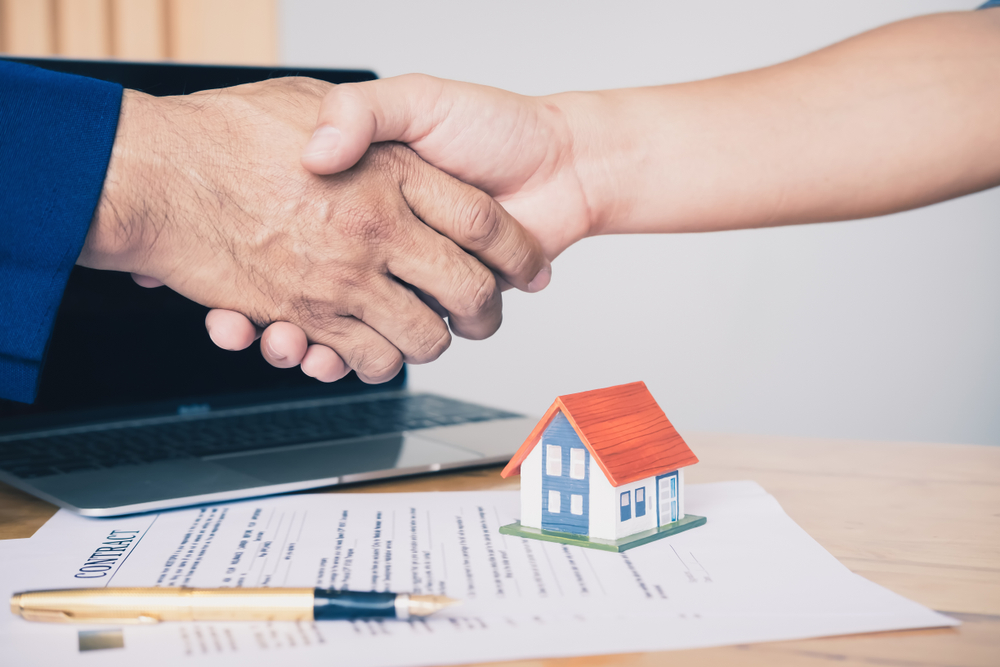 Seller and buyer shaking hands over close documents after a for sale by owner home sale