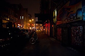 """Photo: """"Mist from the fog of millions of thoughts...""""  At night, as the street lights guide urban wanderers home under a blanket of darkness,  the mist from the fog of millions of thoughts exhales at once into a sky heavy with dreams.  —-  This is a view looking down Rivington Street towards Suffolk Street on the Lower East Side in lower Manhattan. The building in the foreground with the colorful street art and graffiti is ABC No Rio, a center for art and activism that has been in this neighborhood since 1980.  This was taken with the Sony a99. It feels great to capture night scenes with this camera since it performs really well in low-light. During winter here in New York City, the nights seem endless so it's nice to be able to capture what I experience and see on a daily basis after the sun goes down .    New York Photography: Rivington Street, Lower East Side at night.    You can view this post along with relevant links at my photography blog here:  http://nythroughthelens.com/post/40763834082/lower-east-side-at-night-new-york-city-at  - Tags: #photography  #newyorkcityphotography  #nyc  #newyorkcity  #city  #cityphotography  #urban  #urbanphotography  #streetart  #lowereastside  #newyorknoir  #nycnoir  #nycphotography  #nycstreet"""