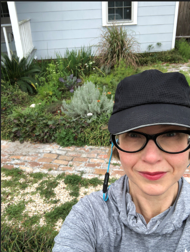 Andrea looks up into the camera, wearing a black baseball cap, black framed glasses and a grey sweatshirt. A brick path and plants are in the background.