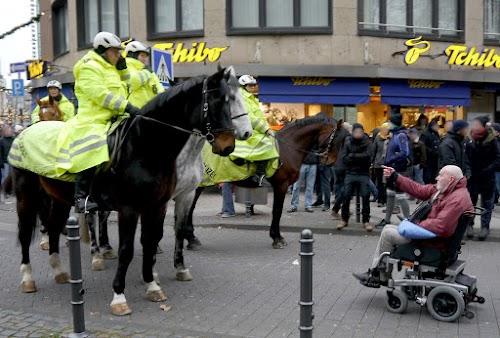 Polizei auf Pferden versperrt Rollstuhlfahrer den Weg.
