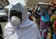 A woman wears a protective mask as she walks along a street in the Adjame area of Abidjan, Ivory Coast.