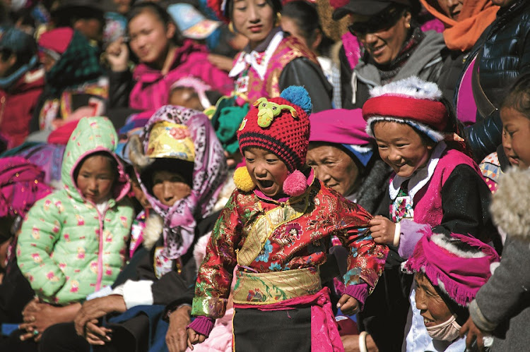 Children in traditional Tibetan clothes watch a dance during the Gedong festival at a monastery in Shangri-La, China. Masked, costumed monks portrayed a host of ghosts and deities from Tibetan Buddhist mythology. Picture: GALLO IMAGES/AFP/JOHANNES EISELE