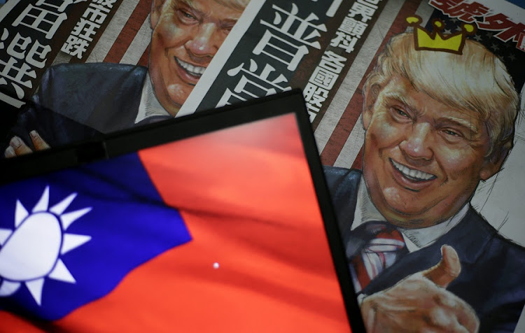 A newspaper headline with an illustration of US president-elect Donald Trump is pictured next to the flag of Taiwan in Taipei, Taiwan. Picture: EPA/RITCHIE B TONGO