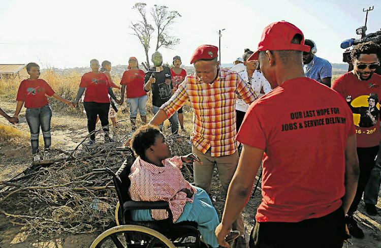 EFF leader Julius Malema listening to Unit P resident Phumelela Kati