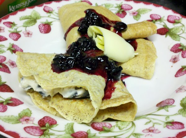 Place 2 Crêpes on serving plate and top with blueberry topping. Add a curl...