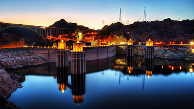 Photo: The Hoover Dam at Sunset  There's something about being at the Hoover Dam watching a sunset that you just can't convey in a photo like this one. Gnats. Billions and billions of gnats swarming all around my head, getting on my lens, and generally wreaking havoc with the peaceful evening I hoped to have that evening.  Like any other sunset I photograph, I was hoping for clouds. It would've been nice, but I generally don't see them in this part of the world early in the year. At least, not the kind of clouds I wanted in the sky. Instead, it was just a cloud of gnats.  If you haven't visited the Hoover Dam before, I'll give you a little tip. Look in the center of the photo at those little rows of glowing orange lights. You pay $7 to park there. Go across the dam to where I took this photo. It's free to park in the lot over here on the Arizona side.  Happy motoring.  Please visit the blog at http://williambeem.com
