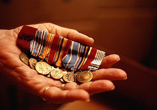 Image for Veteran Home Health Care Discounts Offered by Elders Helpers Hand Holding Military Medals