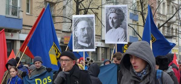 Demonstrierende, rote Fahnen, blaue FDJ-Fahnen und Großbilder von Karl Liebknecht und Rosa Luxemburg.