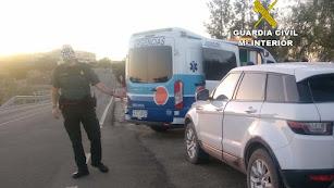 Un agente junto al vehículo del hombre que sufrió la hipoglucemia, ya atendido por una ambulancia.