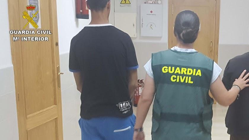 Una agente de la Guardia Civil, con dos detenidos.