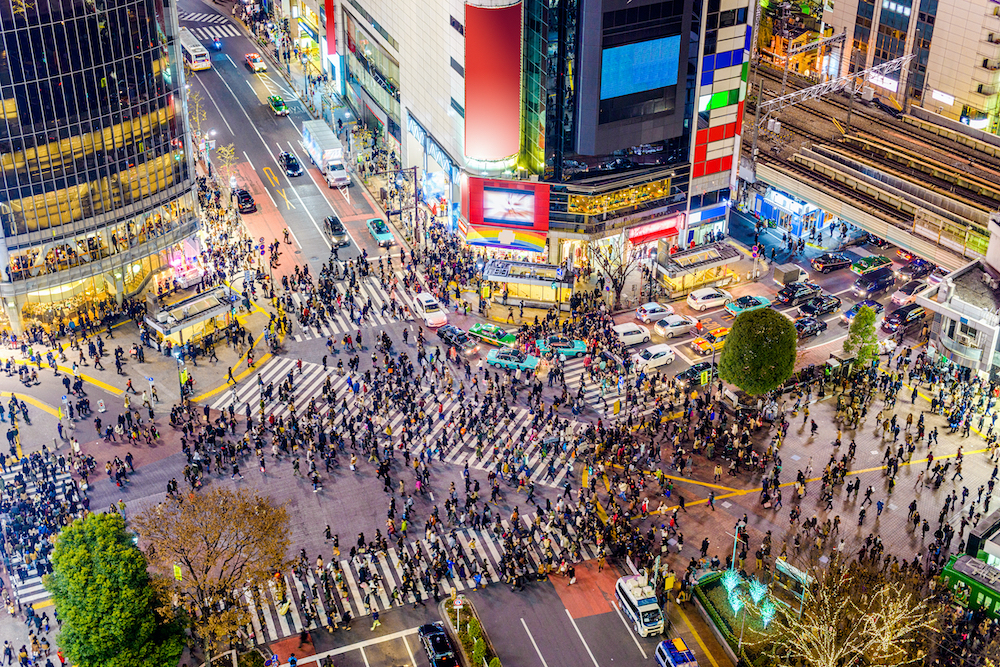 The famous Shibuya crossing in Tokyo, Japan. Hundreds of pedestrians cross the busy intersection at night. Buildings and neon signs surround them.